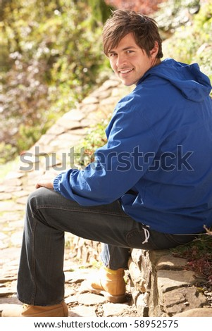 Young Man Relaxing In Autumn Garden - stock photo