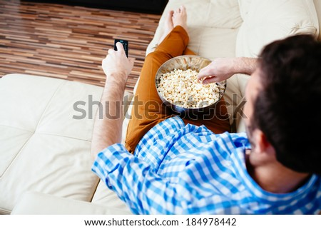 Young man relaxing in front of TV - stock photo
