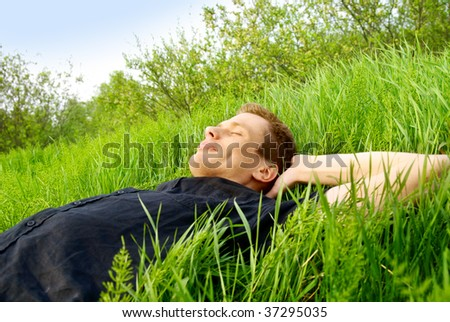 young man relaxing in spring grass