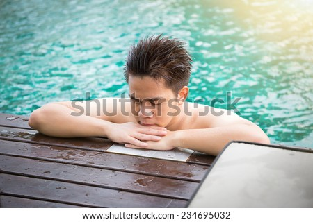 Young man relaxing on a luxury swimming pool - stock photo