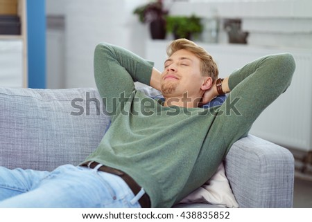 Young man relaxing on a sofa with his hands clasped behind his head and eyes closed