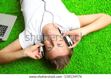 Young man relaxing on carpet and listening to music - stock photo