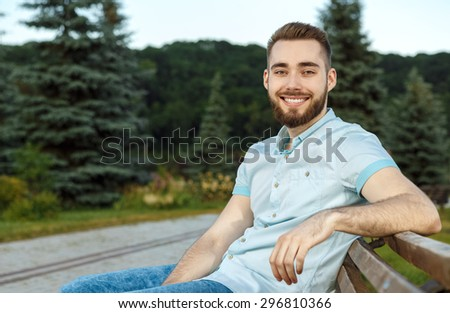 Young man relaxing on park bench