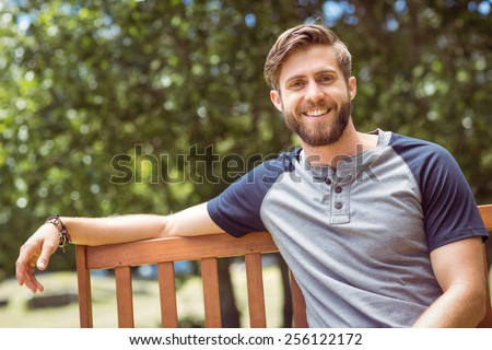 Young man relaxing on park bench on a summers day - stock photo