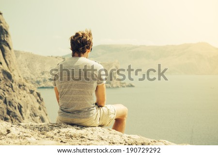 Young Man relaxing on rocky cliff  Sea and mountains on background Lifestyle Summer vacations concept retro colors - stock photo
