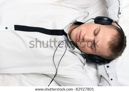 Young man relaxing on the couch listening to music over white background.