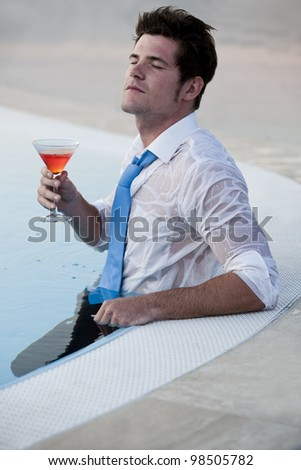 Young man relaxing on the pool with cocktail, his eyes closed