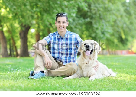 Young man relaxing outdoors seated with his dog