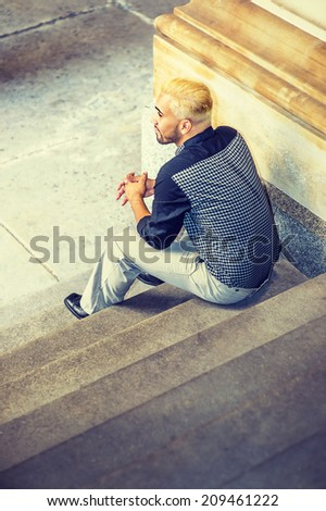 Young Man Relaxing Outside. Wearing a black patterned shirt, grey pants, leather shoes, a young guy with beard, yellow hair, is sitting on stairs, back view. - stock photo