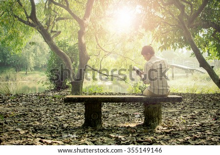 Young man relaxing & reading books alone in a peaceful garden enjoying his leisure in early winter afternoon - stock photo