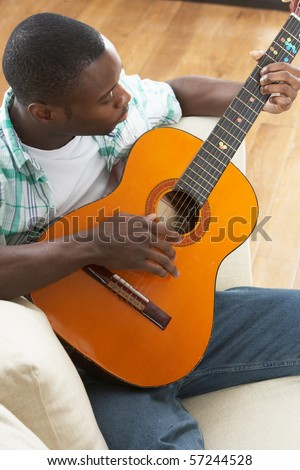 Young Man Relaxing Sitting On Sofa Playing Acoustic Guitar - stock photo