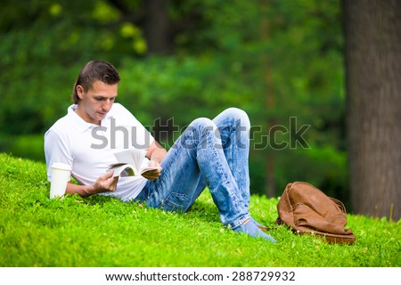 Young man relaxing with coffee in park reading a book - stock photo