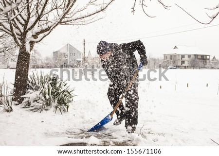 Young man remove snow near the suburban house - stock photo