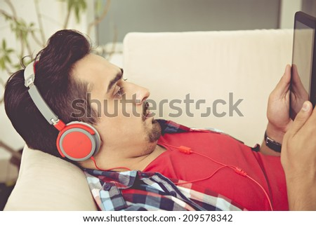 Young Man Resting At Sofa Using Tablet And Listening Music Via Headphones - stock photo