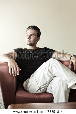 Young man resting on chair.