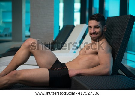 Young Man Resting On Sun Loungers By Swimming Pool And Flexing Muscles - stock photo