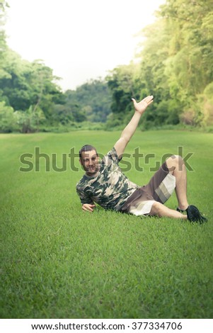 young man resting on the grass with outstretched hand to the sky - stock photo