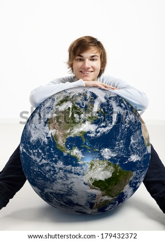 Young man resting over a small planet earth - Image of planet provided by Nasa - stock photo