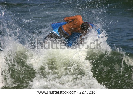 young man rides a wave while body boarding