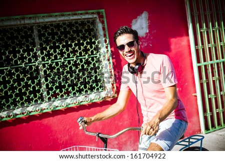 Young man riding a bike across the city with headphones - stock photo