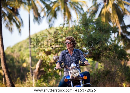 Young man riding a bike during his vacation in Goa, India - stock photo