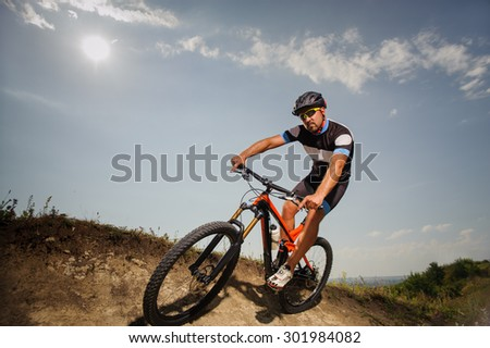 young man riding a bike in the mountains - stock photo