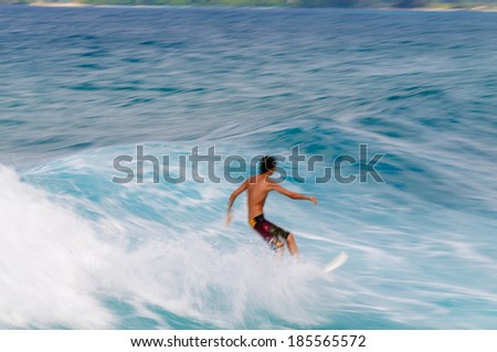 Young man riding a surfboard in a blue wave in the summer. - stock photo