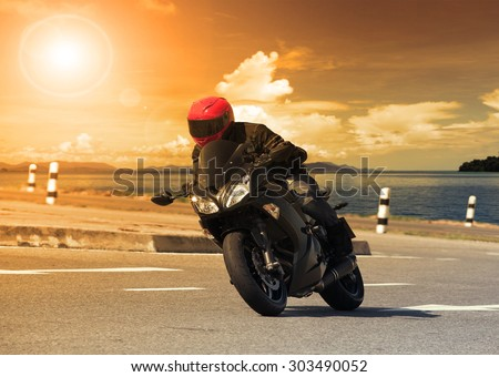 young man riding big bike motorcycle against sharp curve of asphalt high ways road with rural lake scene use for male adventure activities and motor sport hobby on holiday vacation - stock photo
