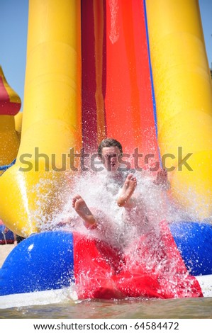 Young man riding down a water slide - stock photo