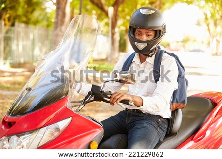 Young Man Riding Motor Scooter To Work - stock photo