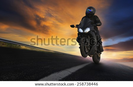 young man riding motorcycle on asphalt highways road with professional extreme biking skill use for sport racing and people vacation activities  - stock photo