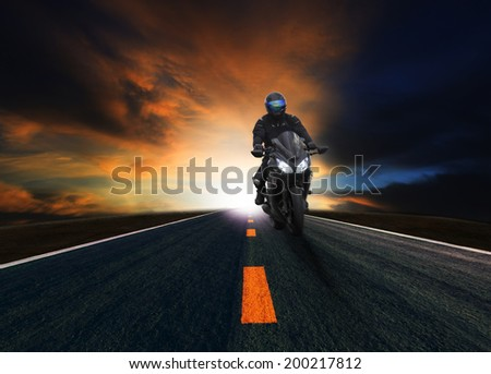 young man riding motorcycle on asphalt road against beautiful dusky sky use for land transport - stock photo