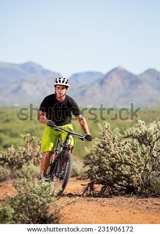 Young Man Riding Mountain Bike in Desert - stock photo