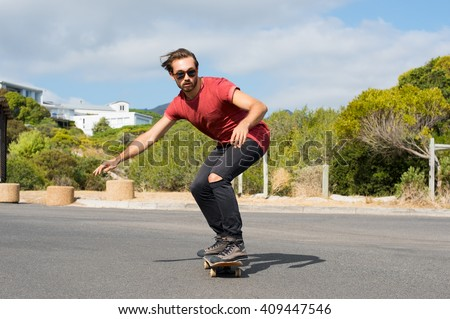 Young man riding on a skate in the city street. Cool skater doing a stunt on his skateboard. Cool street skateboarder in a urban scene. - stock photo