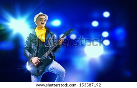 Young man, rock musician in jacket playing guitar - stock photo