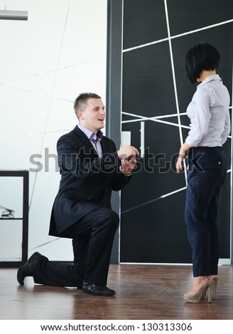 Young man romantically proposing to girlfriend and offering engagement ring at working place - stock photo