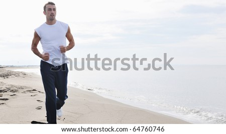 young man running and jogging at early morning on beach - stock photo