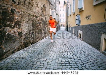 Young man running on a narrow cobbled lane - stock photo