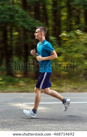 Young man running on a road through the forest with motion blur