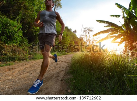Young man running on a rural road during sunset - stock photo