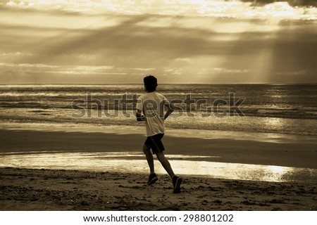 Young man running on beach at sunset. Back view. Dramatic sky lighting with sun rays glowing through the clouds. A game of light and shadow. Aged photo. Sepia.