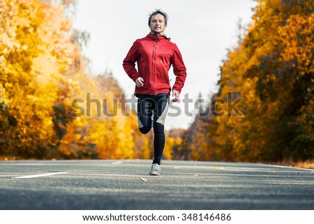 Young man running on the autumn road - stock photo
