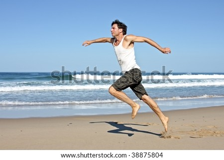 Young man running on the beach - stock photo