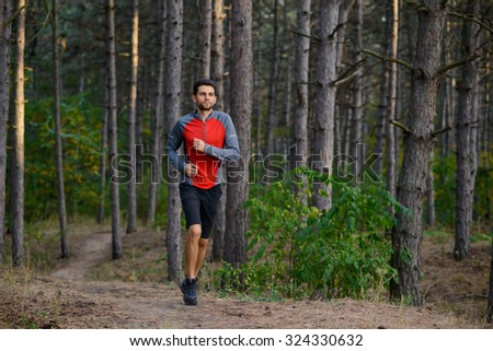 Young Man Running on the Trail in the Wild Pine Forest. Active Lifestyle Concept - stock photo