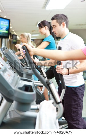 young man running on treadmill at gym - stock photo
