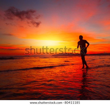 Young man running on wet coastline at bright sunset background