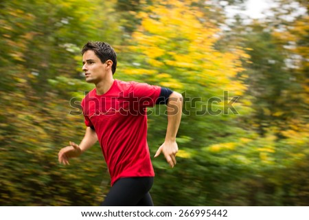 Young man running outdoors in a city park on a fall/autumn day (motion blurred image) - stock photo