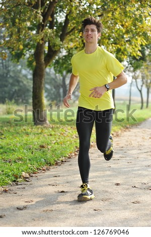 Young Man Running Through Park - stock photo
