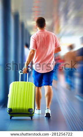 young man runs, hurry in order not to miss the plane, motion blur - stock photo