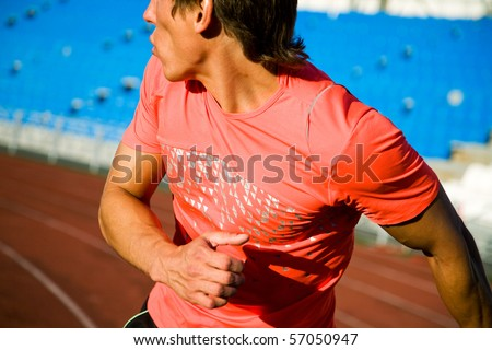 young man runs through the stadium and look back - stock photo